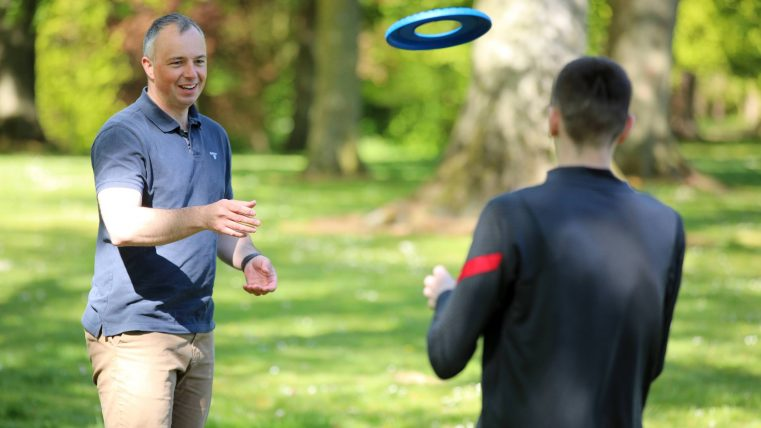 MACS volunteer and young person playing frisbee in the park