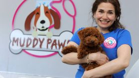 Muddy Paws Volunteer Homeira smiling and holding a cute small brown shaggy dog